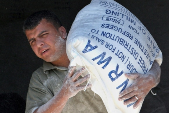 Palestinian carrying sack of flour from UNRWA