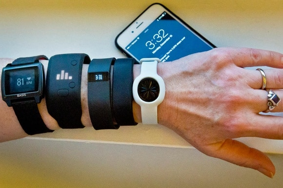 A picture of someone wearing a variety of health tracking devices