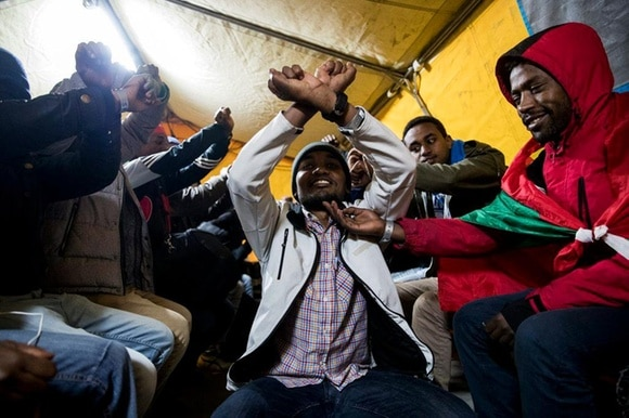 Ethiopian ethnic group Oromo migrants cheering after being evacuated from a makeshift camp in France.