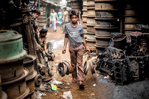 Indian child carrying metal wheels at an automobile reycle market in Calcutta.