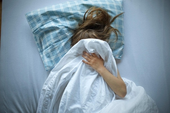 A picture of a girl lying in bed, hiding her face.