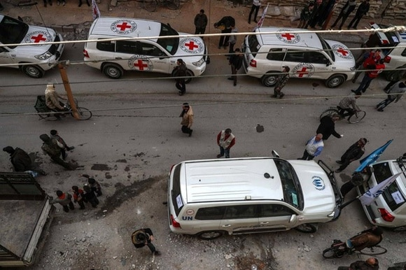 People gather near UN and ICRC cars in a street in Douma, Syria.