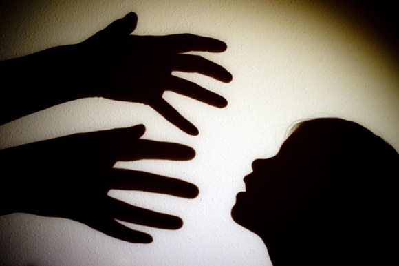 shadow of adult hands coming at face of a child