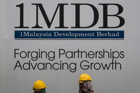 1MDB sign with workmen underneath