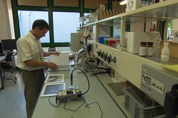 Man looking at ammunition pictures in lab