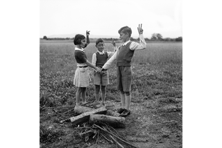Three children standing by wooden logs making a vow.