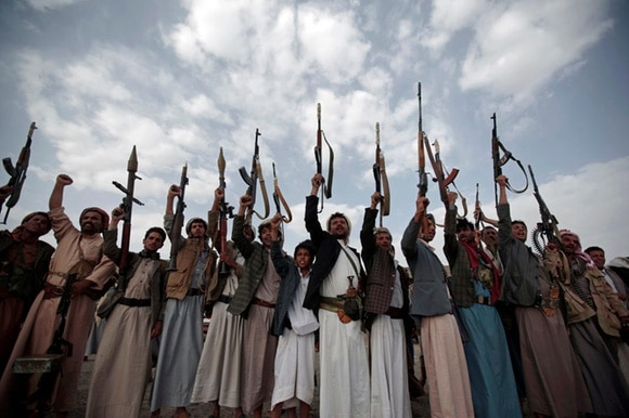 Yemeni gunmen raising their rifles.