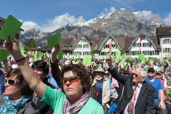 Voters hold up green cards with traditional buildings and houses in background