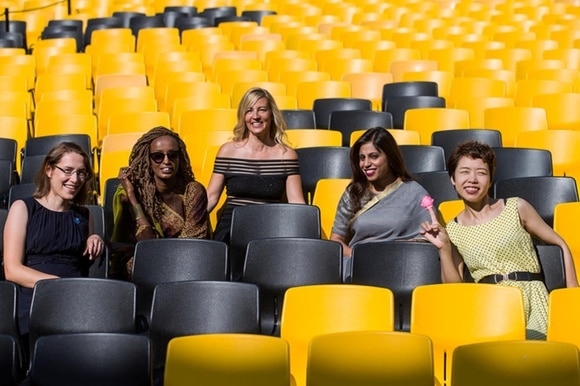 Five women sitting on black and yellow chairs