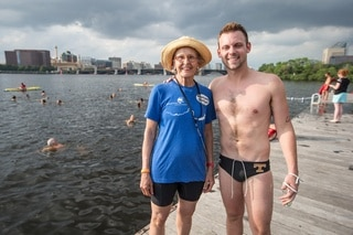Woman and man photographed by the water with swimmers