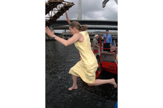 Woman photographed mid-air, while jumping into water