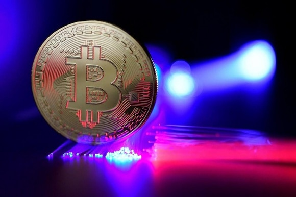 A bitcoin lit up by colourful laser lights