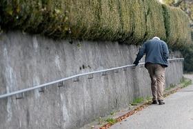Un anziano cammina in salita aiutandosi con il corrimano