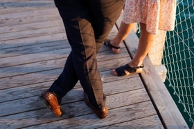 A man, in dress pants and leather loafers, and a woman, in a summer skirt and sandals