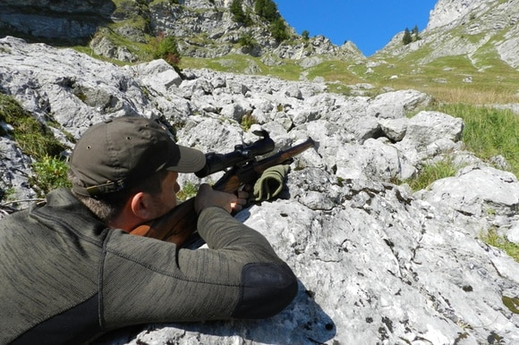 Hunter takes aim with his rifle in the mountains