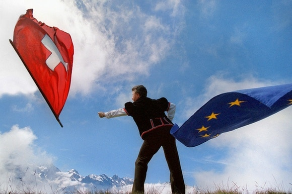 Man in traditional Swiss costume throwing a Swiss and EU flag in the air