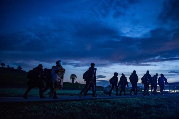 Refugees walking in border region below dark sky