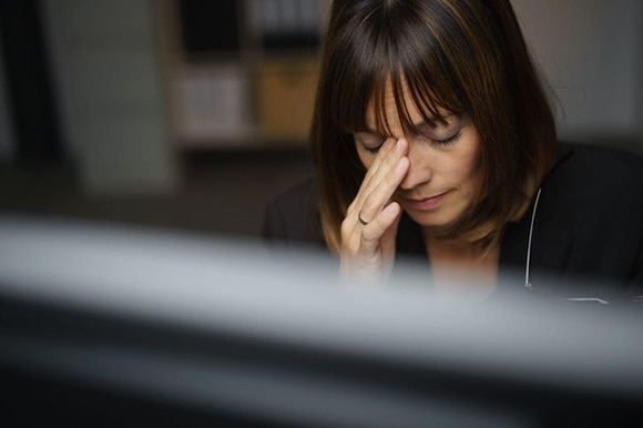 Woman with a headache at work