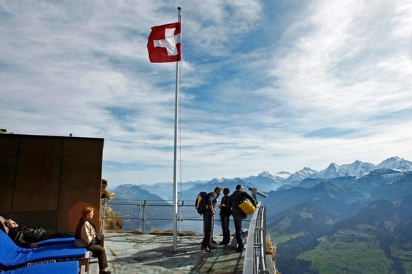 People at the foot of a Swiss flag in the Alps