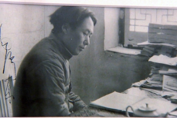 Photo of Mao Zedong sitting at desk