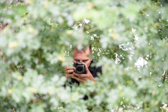 Man with camera hiding behind trees