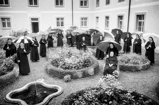 all the nuns in the convent s courtyard with umbrellas