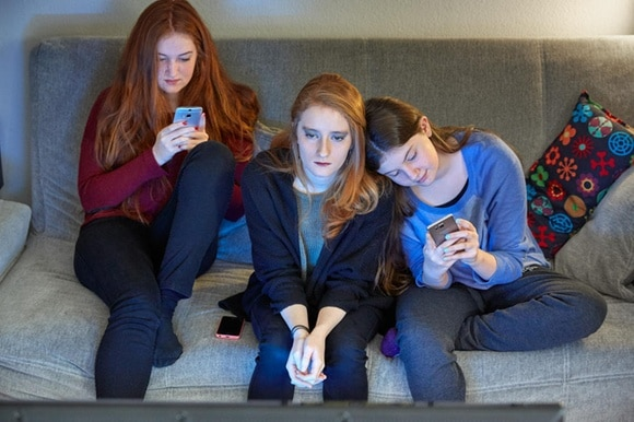 three young girls with smartphones