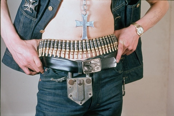 A mans midriff: Bullet belt, belt and padlock