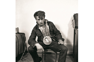 A man sits leaning, with an image of Elvis on a chain around his neck.