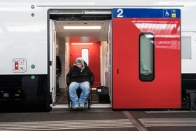 Man in wheelchair exiting train door