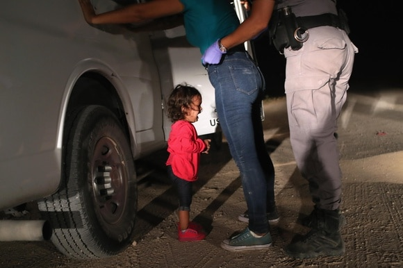 A Honduran child cries while her mother is searched in McAllen, Texas