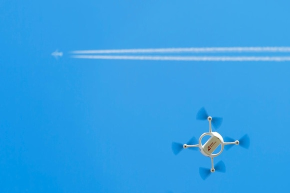 A drone flies in front of an airplane high above in the sky