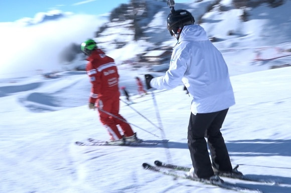 Woman skiing behind indtructor