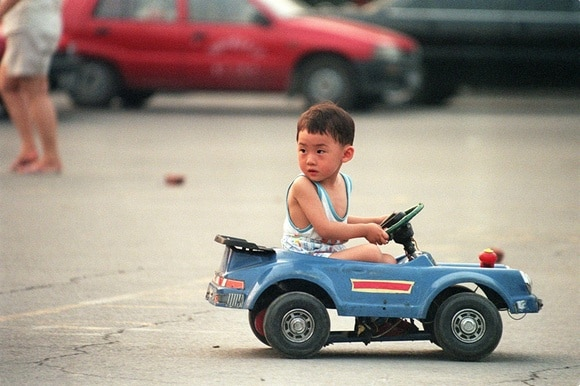 Chinese boy in a blue car