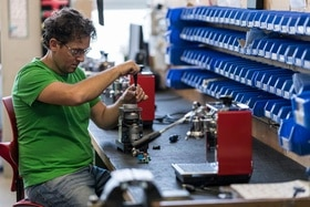 A worker rebuilds a coffee grinder in a factory.