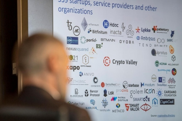 A seated person looks at a chart of Crypto Valley companies
