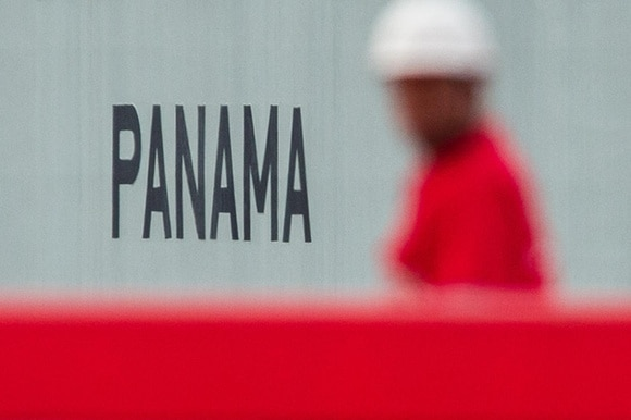A workman walks by a sign saying Panama