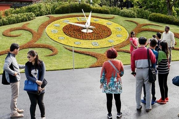 Pessoas em volta de um relógio no jardim