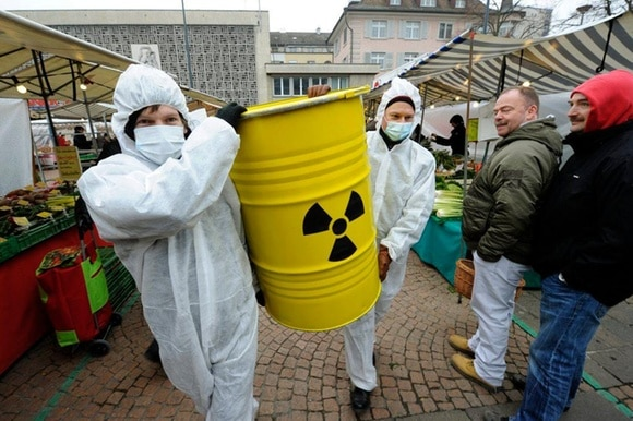 Men carrying nuclear waste container in market