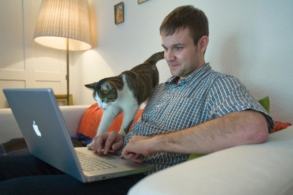 A man looks at his computer with his cat