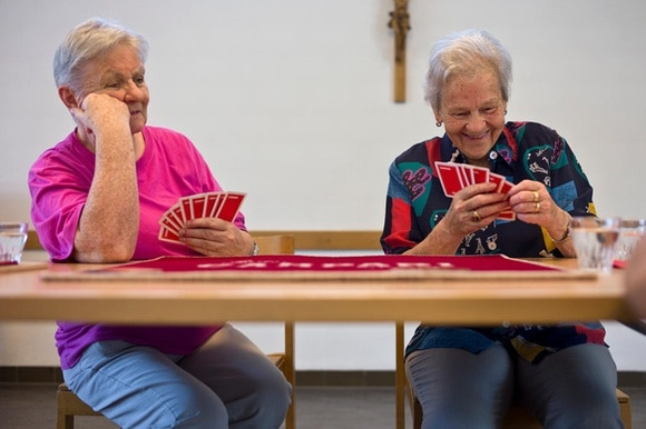 Two older women playing cards