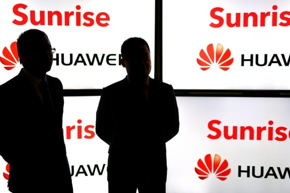 two dark figures against Sunrise Huawei posters