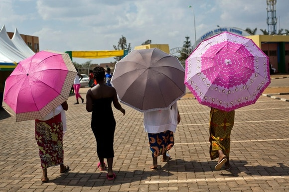 Four Rwandan women with coloured umbrellas