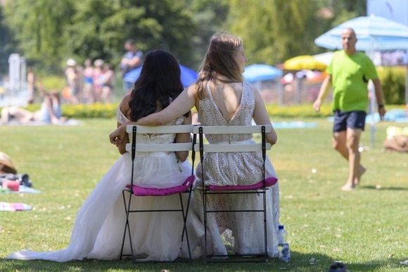 two women in wedding dresses with arms round each other