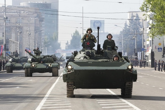 Tanks drive down a road in Donetsk