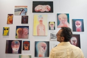A man looking at art by Miriam Cahn at the Art Basel in Hongkong in 2014