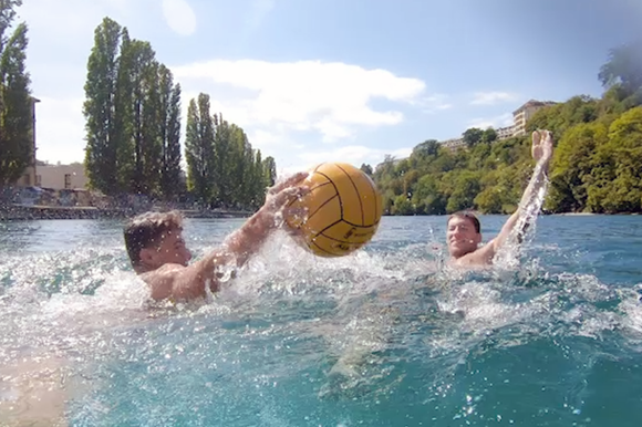 Two men playing with a ball in a river