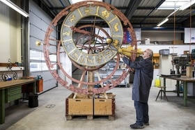 A man repairs the clock and ZYttglogge in Bern