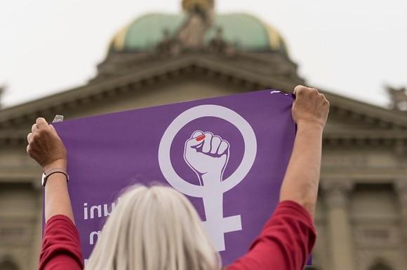 Eine Frau hält an einer Demo ein lila Tuch in die Höhe