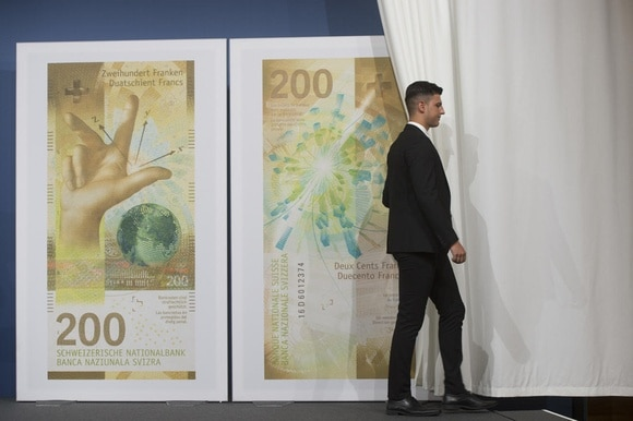 A curtain is drawn open on representations of Swiss francs